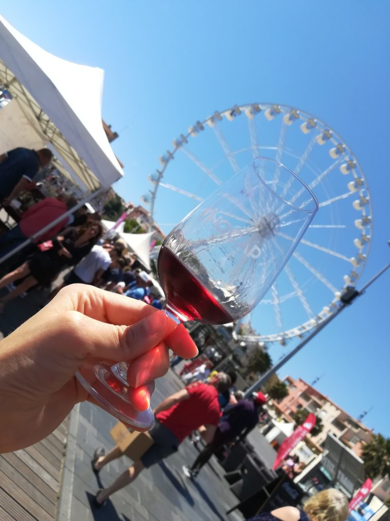 Verre de vin lors du Vinocap 2019 avec la grande roue du Cap d'Agde dans le fond