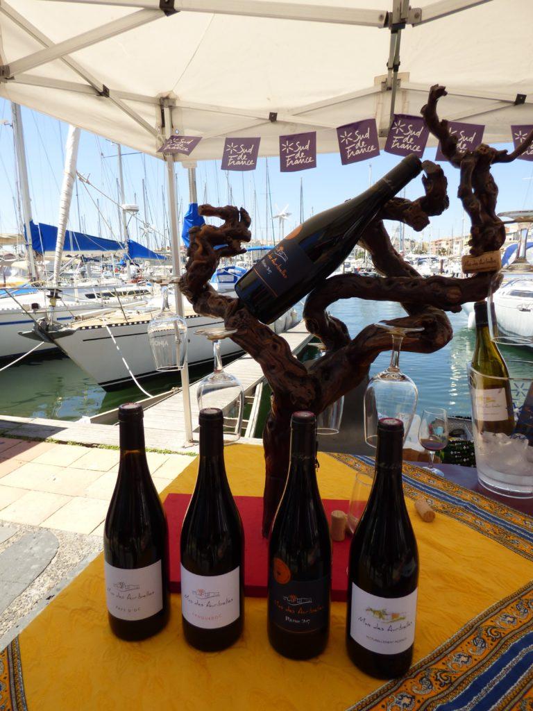 Bouteilles de vin rouge avec un présentoir en cep de vigne au Vinocap 2019